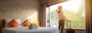 Hospitality Insurance - Modern Hotel Room with Woman Looking Out the Window